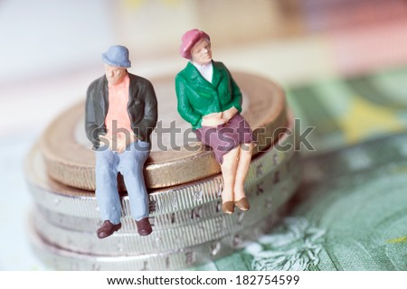 Grandma and Grandpa on a stack of euro coins / Grandma and Grandpa - stock photo