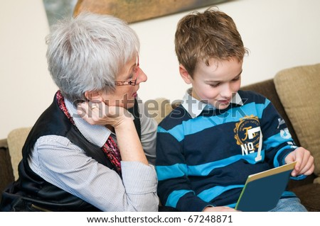 Grandma and grandson are reading a book.