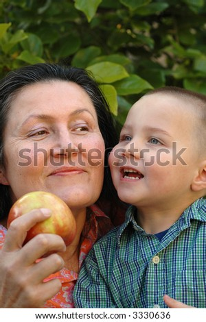Grandma and grandson getting ready to bite into a juicy apple for a snack - stock photo