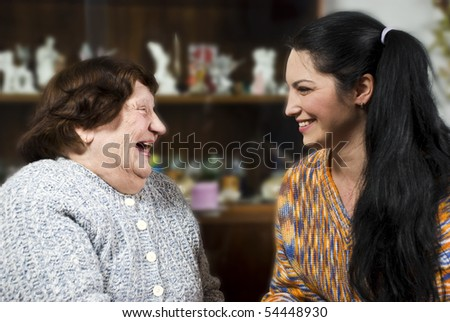 Grandma and her granddaughter having a happy conversation and both laughing together - stock photo
