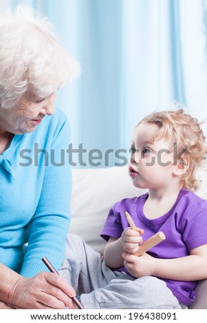Grandma and her grandson drawing together, vertical - stock photo