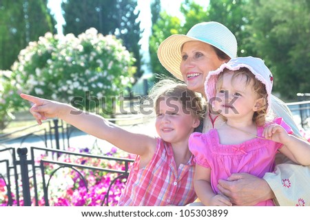 Grandma and her two granddaughters have a rest in the park - stock photo