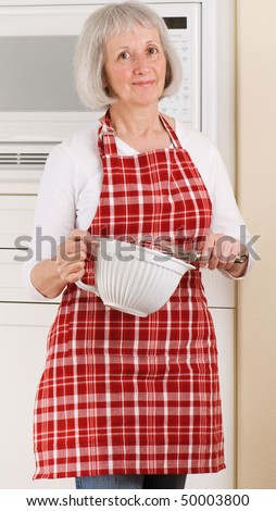 Grandma cooking in her kitchen wearing a red plaid apron - stock photo