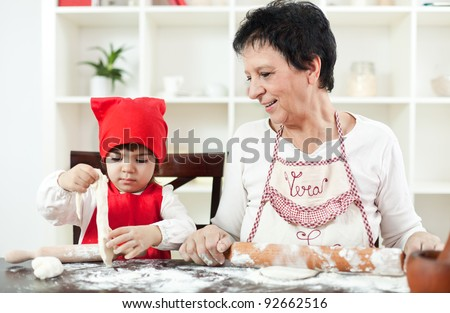 Grandma cooking with her little granddaughter - stock photo