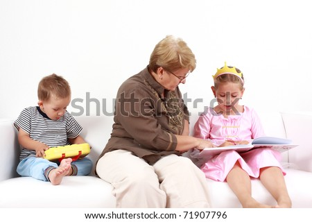 Grandma helping girl by reading and playing with baby - stock photo
