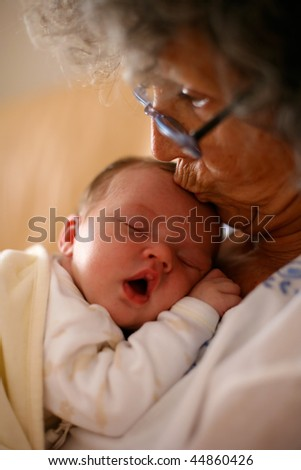 Grandma holding a baby and kissing it on it's head - stock photo