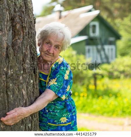 Grandma hugging a tree near rural home. - stock photo