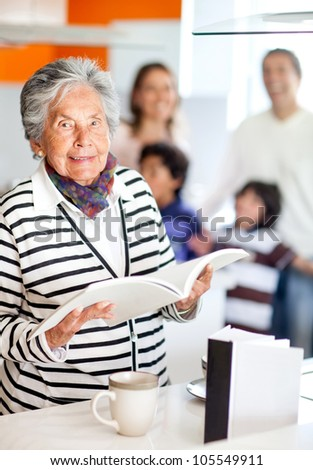 Grandma in the kitchen holding a recipe book - stock photo
