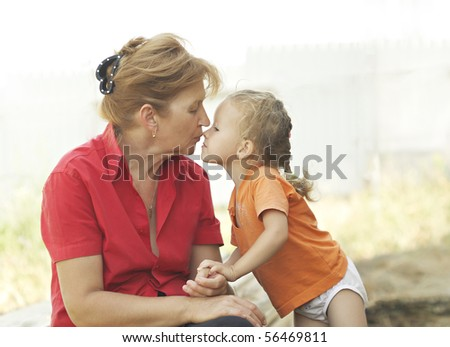 Grandma kisses granddaughter. They sit under the open sky on a summer day. - stock photo