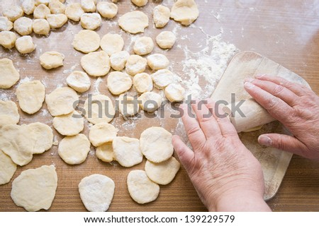 Grandma's hands roll out the dough on wooden table - stock photo