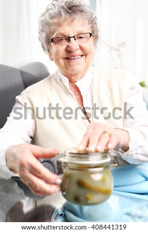 Grandma's preserves, delicious place the jars for the winter. Mature woman with jars personally prepared products.