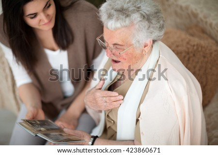 Grandma showing old photo album to her granddaughter - stock photo