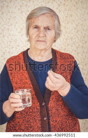 Grandma taking pills with a glass of water - stock photo