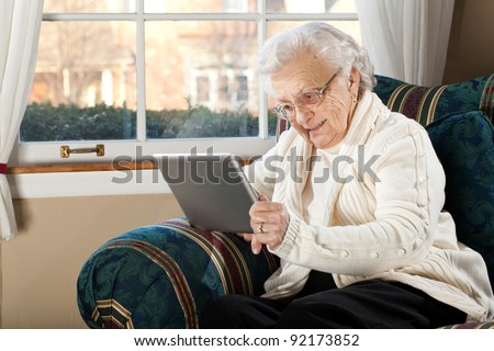 Grandma Using Tablet PC in Living Room - stock photo
