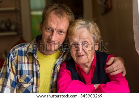 Grandma with her adult grandson, portrait close-up. - stock photo