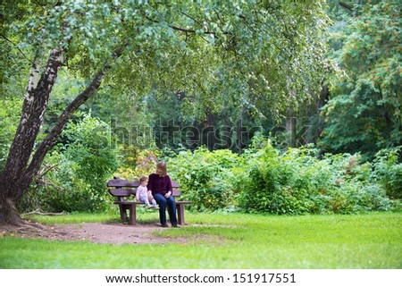 Grandmother and baby girl relaxing in a park on a bench under a big beautiful tree on a warm autumn day - stock photo