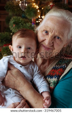 Grandmother and baby toddler, her grandson near Christmas tree, indoor - stock photo