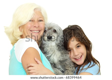 Grandmother and girl hugging the family dog isolated on a white background - stock photo