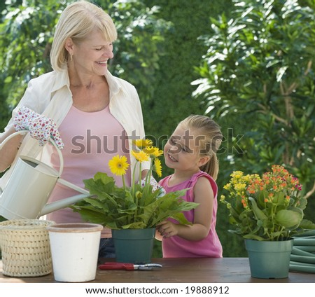 Grandmother and grand daughter watering plants - stock photo