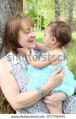 Grandmother and grandaughter sitting outside in the field - stock photo