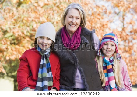 Grandmother and grandchildren on autumn walk - stock photo