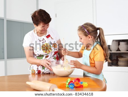 Grandmother and granddaughter baking and having fun together - stock photo
