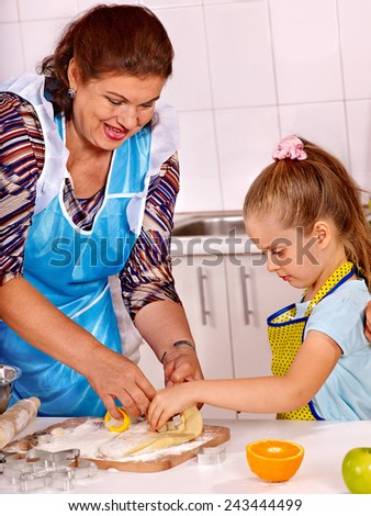 Grandmother and granddaughter baking cookies.