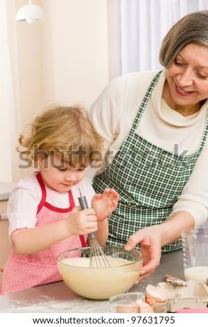 Grandmother and granddaughter baking cookies prepare dough - stock photo
