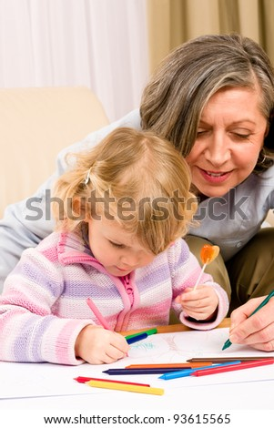 Grandmother and granddaughter drawing together with pencils - stock photo