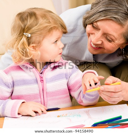 Grandmother and granddaughter drawing together with pencils at home - stock photo