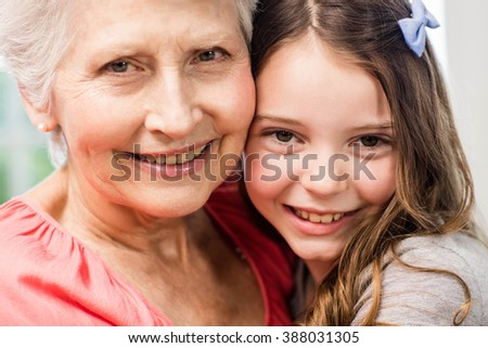 Grandmother and granddaughter embracing at home - stock photo