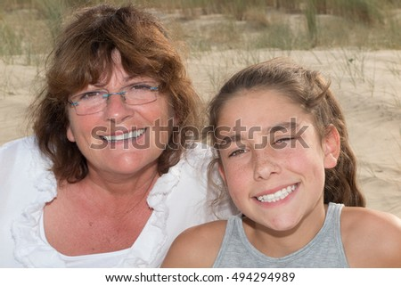 Grandmother and granddaughter embracing at the beach