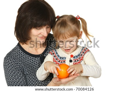 Grandmother and granddaughter going to peel an orange - stock photo