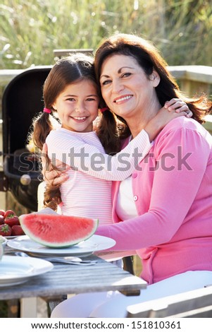 Grandmother And Granddaughter Having Outdoor Barbeque