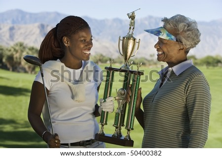 Grandmother and granddaughter holding golf trophy, smiling - stock photo