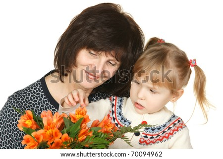 Grandmother and granddaughter intently looking petals of flowers isolated on white - stock photo