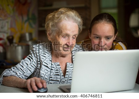 Grandmother and granddaughter learn to work on computer. - stock photo