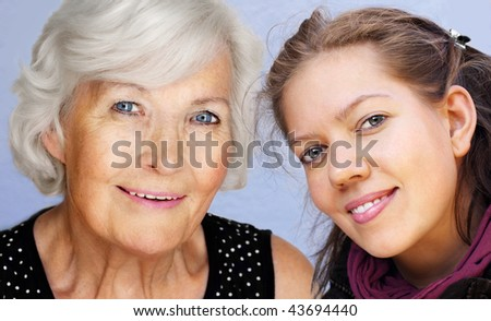 Grandmother and granddaughter looking at camera together,smiling - stock photo