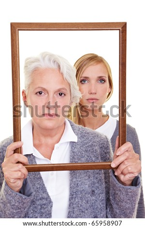Grandmother and granddaughter looking seriously through an empty frame - stock photo