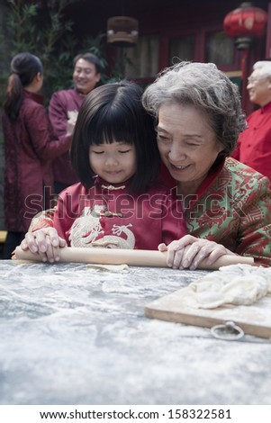 Grandmother and granddaughter making dumplings in traditional clothing - stock photo