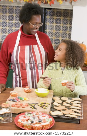 Grandmother and granddaughter making Halloween treats and smiling - stock photo