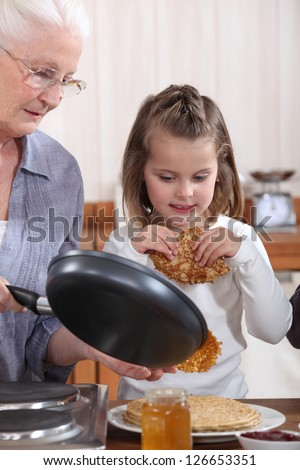 Grandmother and granddaughter making pancakes - stock photo