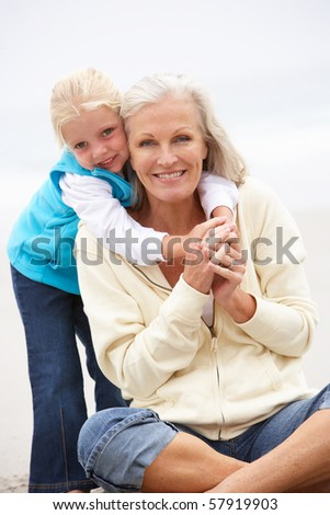 Grandmother And Granddaughter On Holiday Sitting On Winter Beach