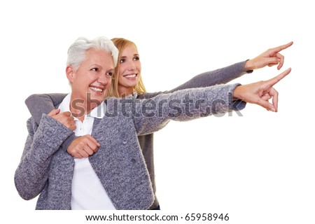 Grandmother and granddaughter pointing with their index fingers - stock photo