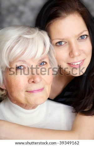Grandmother and granddaughter portrait, embraced  and smiling at camera - stock photo