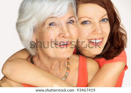 Grandmother and granddaughter portrait, embraced  on white background - stock photo