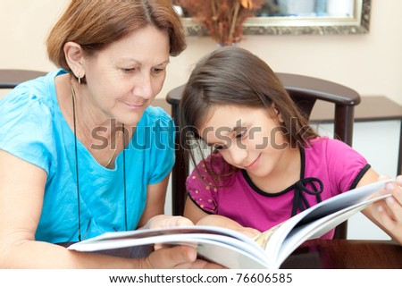Grandmother and granddaughter reading a book at home - stock photo