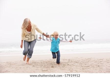 Grandmother And Granddaughter Running Along Winter Beach - stock photo