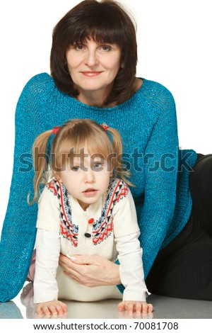 Grandmother and granddaughter sitting on the floor - stock photo