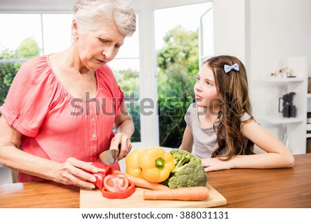 Grandmother and granddaughter slicing vegetables in the kitchen - stock photo